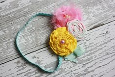 Pink, teal and yellow ava ribbon ruffle, rosette and chiffon flower headband. $15.50, via Etsy. Birdie Baby Boutique.