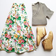 white and black striped top, white and multicolored floral skirt, and tan ankle boots