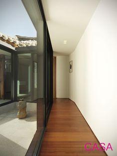 Elongated hallway in small Korean traditional house, Hanok. Reclaimed stone in inner garden. 서촌 한옥 일본식 마당
