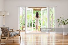 Stock Photo : Hispanic woman opening French doors to patio