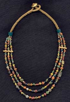 by Katie Singer   Necklace; 1,000 year-old glass beads from the area now called Thailand, Vermeil gold, handwoven cord   {Price not published, please contact seller}