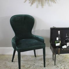 Stunning cocktail chair, upholstered with a rich emerald green velvet.The sleek shape of the chair will compliment a modern theme and makes a luxury statement.It is constructed with a metal frame and has matching upholstered velvet legs.