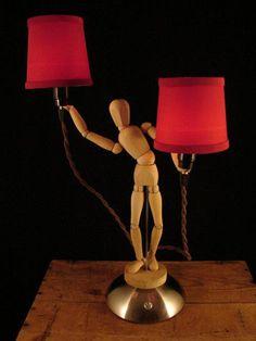 Muñeco de madera sosteniendo dos lamparas