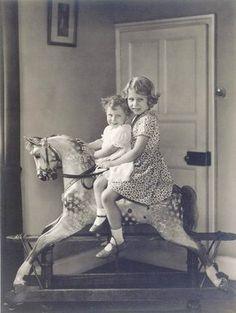 Princess Elizabeth and Princess Margaret riding a rocking horse at St. Paul's…