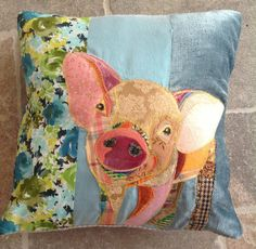 A  blue background, handmade, appliqued pig cushion made from vintage and new fabrics