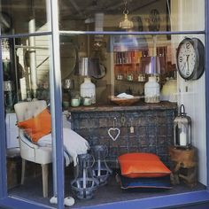 Period Indian chest, orange and teal velvet cushions,  button studded bedroom chair, blue black industrial style pendant light.