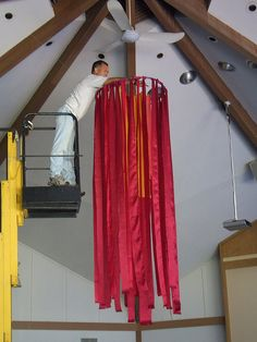 "Hanging the Pentecost ""flames"" made from cut strips of red and orange fabric on a hula hoop. Fishing line was criss-crossed across hoop to fill in the center with fabric strips."
