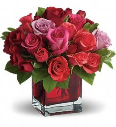 A Bold mixture of Coral Sweetheart Roses and Lavender & Pink Roses arranged in a red-hot cube vase are an absolutely beautiful way to say 'I Love You.'  T9-3A