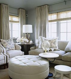 Ideas for Multiple Windows -- Tailored silk panels add a touch of glamour to this modern living room. Woven wooden roller shades add a casual flair to the window treatment. Because the roller shades come in various widths, these windows are able to have matching treatments despite being two different sizes. Now the room has a sleek, uniform look.