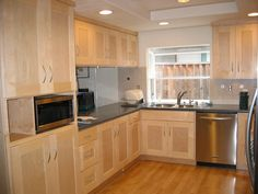 light maple shaker cabinets…My kitchen is much smaller but this is what I am having built….with rubbed bronze handles