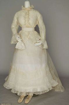 1868 two-piece wedding dress, linen hankie, and white silk slippers w/ rosettes: white organdy w/ Valenciennes lace on fitted jacket and trained skirt worn by Louise Loomis Burrell of Little Falls, NY, on December 30, 1868.
