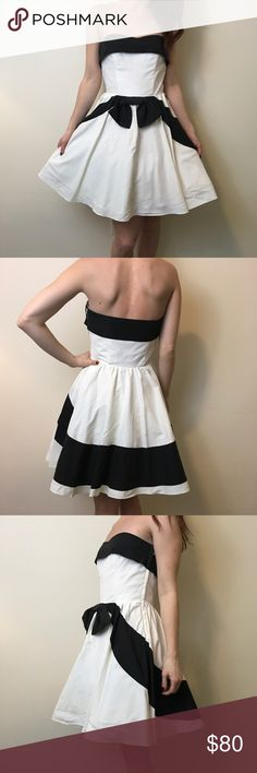 """Betsey Johnson White & Black Strapless Party Dress Betsey Johnson Evening gown with a gorgeous outer body that is white with black ribbon printed stripes and is poofy and Flouncy at the bottom- knee length! Lined and has Tulle underneath. A size 4. Worn once but needs a dry cleaning has some light marks but nothing noticeable but just shows on white a little off white. Don't miss this beauty! Bust flat measures 15"""" waist 13"""" hips free and length 27"""" Betsey Johnson Dresses Strapless"""
