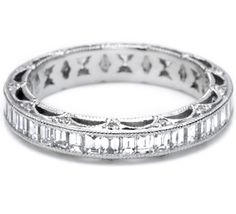 Platinum and diamond straight eternity band, pictured with channel-set baguette diamonds on the top of the band and pave-set round diamonds accenting the arching crescent silhouette details on the top and bottom of the band.