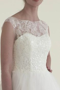 """All eyes will be on you as you walk down the aisle in this stunning ball gown!  4"""" extra length gown.  Available for special order only in White and Ivory in stores and online.  Cap sleeve tulle ball gown features ultra-feminine illusion neckline.  Bodice is adorned with beaded lace appliques.  Chapel train."""