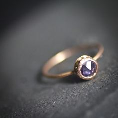 This ring is a handmade and handset. Custom alloyed color of 14 karat rose gold.  A 2mm band size featuring 4.5-5 mm natural purple rose cut sapphire. Surround by 14 bread set 1.3 mm Natural Yellow diamonds.  rose gold, ethical wedding, jewelry,engagement ring
