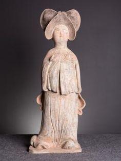 Figurine funéraire chinoise « Mingqi » représentant une dame de cour, plus connue sous la dénomination de « Fat Lady » en raison de ses formes généreuses.  Statuette debout en terre cuite à engobe crème à traces de polychromie noir et rouge, les mais jointes sous ses larges manches contre son ventre et portant un chien.  Dynastie Tang. Début 7ème Siècle (618 AP.J.-C.)au Début 10ème Siècle (907 AP.J.-C.)  Datation C.815 (+/-25%) Confirmée par un test de thermoluminescence du laboratoire R