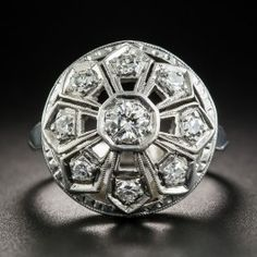 This unique and unusual late-Art Deco dinner or cocktail ring, circa 1930s-40s, sparkles in all directions in a striking geometric sunburst design with eight round diamonds radiating outward from a larger center stone. The gently domed top makes artful use of negative space. Hand-fabricated in 14K white gold, 11/16 inch diameter. Currently ring size 5 1/4.