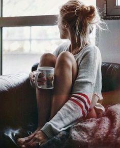 Tendência Hygge mulher segurando xícara na mão e sentada no sofá