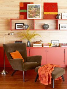 Retro Red. Layered shades of red and brown mingle to add dimension to this space. The horizontal wood paneling and red cabinets give off a warm, retro vibe. Backless shelving offers a display for art and photographs.