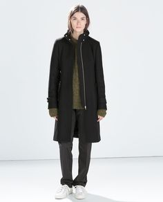 Zip Pocket Coat - Long black coat. Straight cut with a belt and snaps at the collar and cuffs. Concealed zips and zipped flap pockets.
