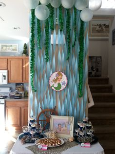 Blue paper streamers and green ruffled streamers serve as a sea-worthy backdrop behind the sweets table.