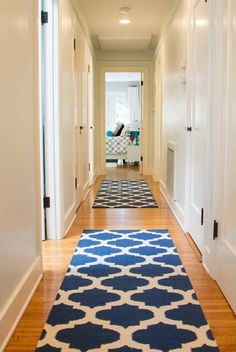 Cobalt-blue Moroccan-inspired rugs line this transitional hallway, adding color and style to the neutral space. The rugs also help to soften the hardwood floors, ensuring the space feels inviting and homey. Flur Design, Tapis Design, Trellis Design, Long Hallway Runners, Long Runner Rugs, Rug Runners, Stair Runners, Hallway Designs, Hallway Ideas