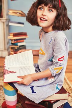 Matilda's been up to her tricksy games again: she's used her special telekinetic powers on this easy-to-wear, pure-cotton jersey dress. Just look at the rainbow of letters flying all over it (which have been decorated with textured appliqué and sparkly sequins). She's even added an inside-collar trim in 'Miss Honey' yellow. If you see her, can you tell her she's got some explaining to do?