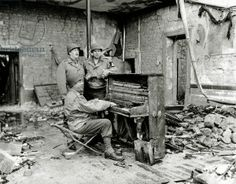 Three GIs are in a devastated house with a completely dilapidated piano. 6th July 1944. These men are not armed and are wearing new uniforms. The man leaning on the piano is a non-combatant civilian employee working for a company under contract with the armed forces or a civilian employed by the War Department. They could be members of Operation Crossbow during their visit to Valognes, Normandy, France, 1944
