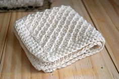 A hand knit daisy stitch washcloth pattern, finished with a simple crochet edge