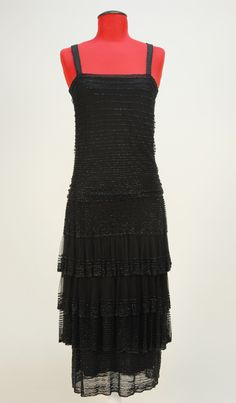 "Cocktail Dress, Chanel, Paris: 1920's, French, silk chemise with wide straps, irregular horizontal bands of jet beads on tulle bodice overlay, four-tier skirt with three applied graduated ruffles, bodice top reinforced with wide grosgrain ribbon.    Label: ""Gabrielle Chanel Paris"""