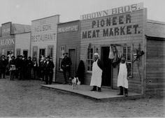 Close-up view of Broadway Street, Round Pond, Okla. Terr. Shopkeepers and customers pose in doorways. By Kennett, January 1894