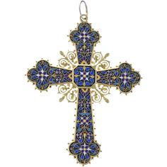 An Antique 18 karat gold and enamel pendant cross with lapis lazuli. The pendant cross is in a Renaissance Revival style, intricately enameled and backed with lapis lazuli with inlaid gold. Hair locket.   Circa 1870's.