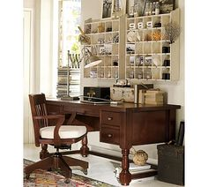 Shelving installed above a desk pushed against the wall. The desk is gorgeous and the shelving is cubby-licious.