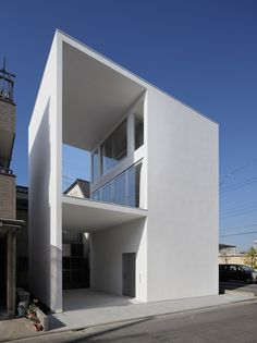 A pair of large terraces channel through one side of this white house in Tokyo by Takuro Yamamoto Architects, providing residents with an outdoor yoga space and a sheltered parking area.