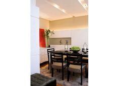 """O """"rasgo"""" no teto de gesso recebeu lâmpadas dicroicas e valorizou a sala de jantar. O painel decorativo abre espaço para nichos e é ressaltado pela iluminação embutida"""