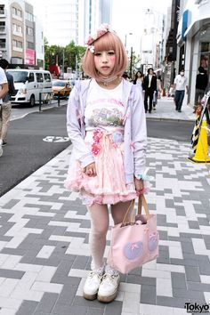 """Haruka is wearing a pastel bow-decorated hoodie over a """"Snow White"""" top with a pink tulle skirt, fishnet stockings, and creepers with crosses (and wings on the back). Accessories include a flower crown, hair bow, lace choker, """"it's a girl"""" button, heart-shaped sunglasses, a strawberry, and a cute double-heart tote bag."""