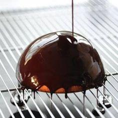GLAÇAGEM BRILHANTE DE CHOCOLATE: 80ml de água 240g de açúcar refinado 80g de cacau em pó 160g de creme de leite fresco 12g de gelatina. Leve ao fogo a água e o açúcar até 103ºC. Adicione o cacau peneirado e mexa, adicione a gelatina hidratada e o creme de leite e misture até ficar homogêneo. Deixe resfriar até 20ºC-25ºC e utilize para cobrir doces ou mono porções!