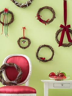 That lovely solid-color wall in your living room makes the perfect canvas for a holiday display. Here, miniature grapevine wreaths add texture to a green wall. We chose a variety of accents -- faux birds, small ornaments, sprigs of berries -- and glued them onto the wreaths before hanging the displays from lengths of ribbon. /