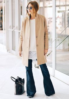 Blogger Maja Weyhe of Maja Wyh wears a white t-shirt layered under a white sweater with flared jeans, a camel coat, leather tote, and Ray-Ban sunglasses
