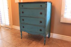 A refinished antique dresser in weathered turquoise with a refinished, yet rustic top, using the original hardware.