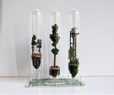 Minúsculas árvores e habitações são os cenários dos pequenos mundos que a artista holandesa Rosa de Jong cria dentro de tubos de ensaio.