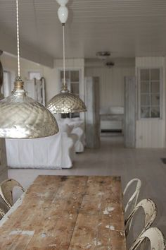 i love the well loved chairs and table… those metallic light fixtures are also quite lovely