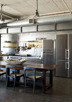 In a loft renovated by designer Andrea Michaelson, a Liebherr refrigerator blends in with stainless-steel cabinets from Fagor featuring Calacatta Paonazzo countertops. Flow chairs by Henry Hall Designs and CB2 benches pull up to an antique farm table.