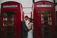 Wedding couple between red telephone boxes. National Telephone Kiosk Collection at Avoncroft Museum of Historic Buildings (avoncroft.org.uk). Summer wedding. Fjona Wei-ling Photography
