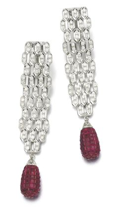 Diamond and ruby earrings. Each designed as a series of articulated links, set with brilliant-cut diamonds, suspending drops set with calibré-cut rubies. Sotheby's.