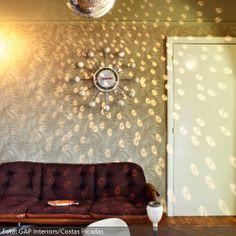 Wer gern feiert, aber keine Lust hat, los zu ziehen, kann mit einer Diskokugel im Wohnzimmer seine ganz eigene Hausparty schmeißen. Für eine chillige Sitzecke im Retro-Style sorgen das violettfarbene Sofa, ein origineller Aschenbecher sowie der dazu passende Beistelltisch, der auch als Hocker genutzt werden kann. Wann es Zeit für die nächste Happy Hour ist, zeigt die weiße Uhr an der Wand an.