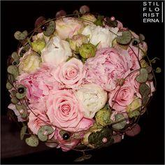 Elegant handbunden och kompakt brudbukett med rosa rosor och pioner i olika nyanser.