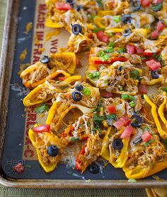 Mini Pepper Chicken Nachos ~ 1 1/2 cups shredded cooked chicken ~ 1 pound mini bell peppers ~ 1 1/2 cups shredded cheddar/Monterey jack cheese blend ~ 1 cup salsa ~ 6 green onions ~ 1/2 large tomato ~ 1/4 cup sliced black olives ~ 1/4 cup cilantro ~ 2 cloves garlic, minced ~ 1 teaspoon chili powder ~ 1 teaspoon vegetable oil