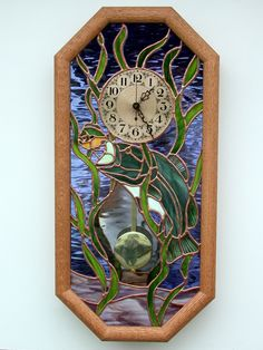 This is my Bass clock.  The Big Mouthed Bass is going after a Pumpkinseed Sunfish.  The wall clock has a handcrafted stained glass face and sports a pendulum quartz clockworks.  Measures 23 1/2 x 11 1/2 with a red oak frame.  $375 + S&H of $25.