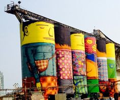 Twin brothers and Brazilian artists Octavio and Gustavo Pandolfo, known together as Os Gemeos, just finished their latest project – a colossal mural covering six industrial silos on Granville Island in Vancouver, Canada. The mural, which is part of the Vancouver Biennale, depicts six vividly colored 70 foot (23 meter) tall characters. The six silos are wrapped all the way around,giving it a total area of 23,500 square feet (7,200 sq meters).